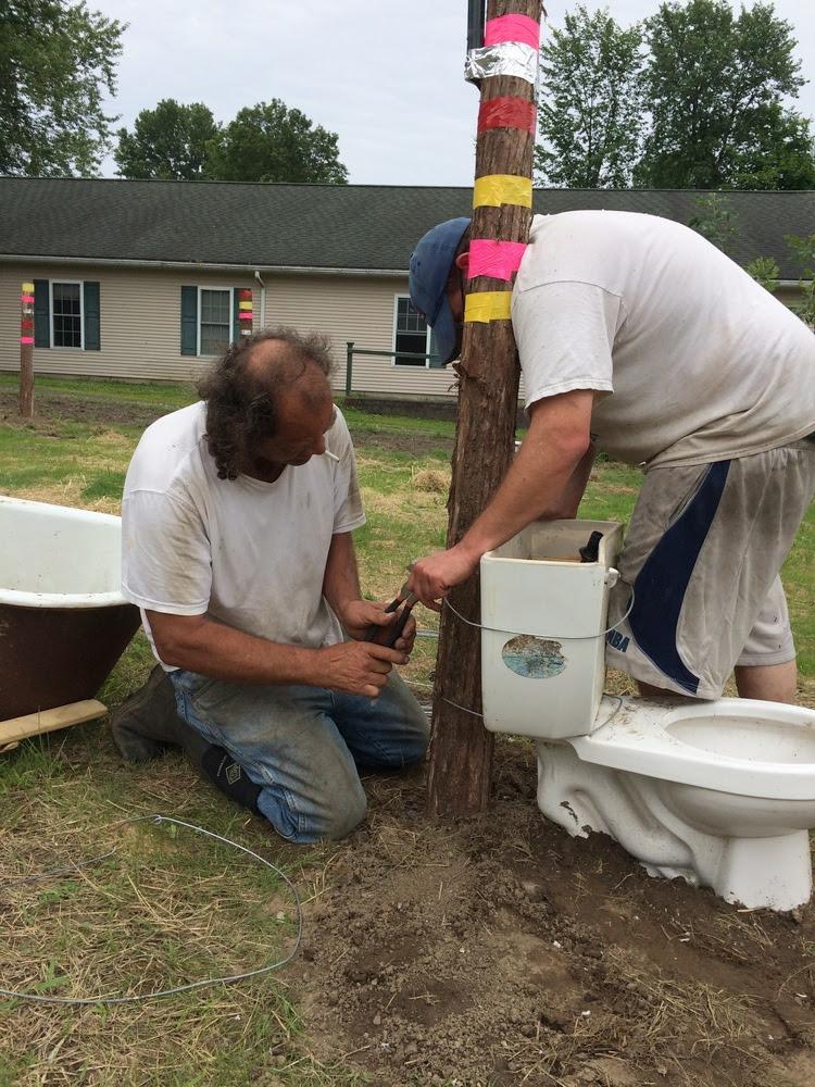 Hank's Helpers, Travis and Joe, secure a toilet.