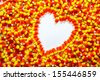 Background of candy corn with heart shape - stock photo