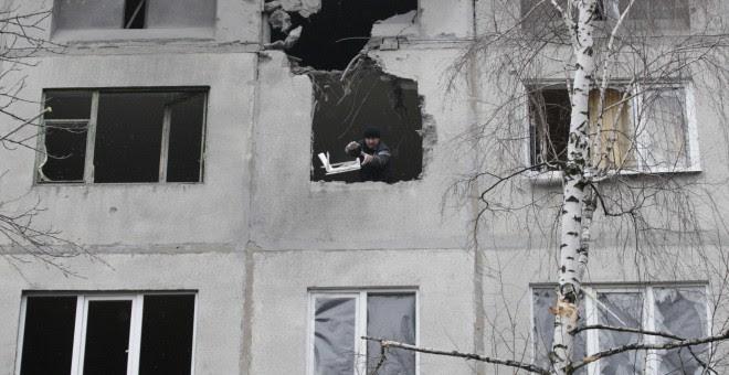 Un hombre lanza escombros desde un edificio en ruinas por los estragos de la guerra en Ucrania./REUTERS