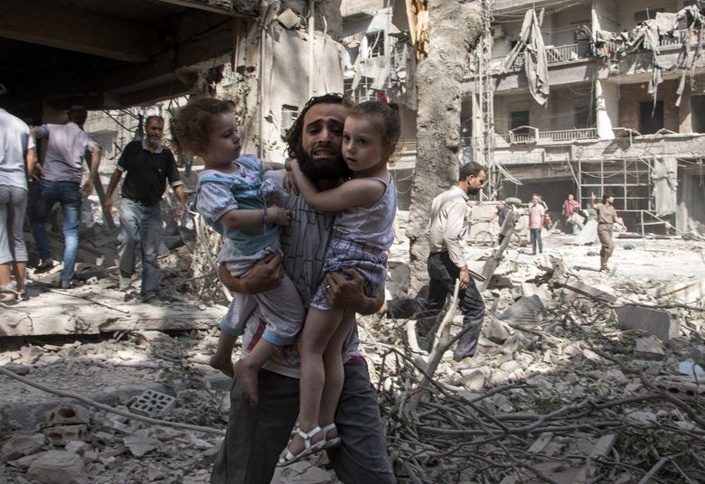 A Syrian man carries his two girls as he walks across the rubble after a barrel-bomb attack on the rebel-held neighborhood of al-Kalasa in the northern Syrian city of Aleppo on Sept. (KARAM AL-MASRI/AFP/Getty Images)