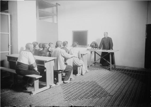 Empleados del cultivo de gusanos de seda reciben clases del cura en el Monasterio de San Bernardo en Toledo en 1925.