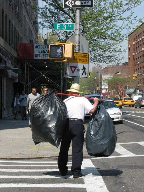 man with bags on 3rd Street, Manhattan, NYC
