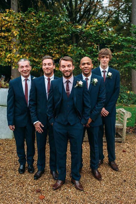 Groomsmen in three piece navy suits with maroon ties