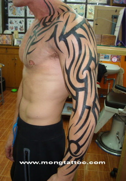 Black Ink Tribal Tattoo On Man Chest And Left Arm