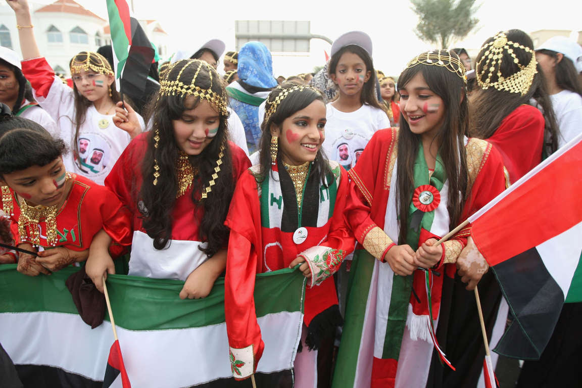 DUBAI, UNITED ARAB EMIRATES - DECEMBER 01:  Girls in traditional UAE dress laugh as during a Dubai National Day parade on December 1, 2008 in Dubai, United Arab Emirates. National Day festivities traditionally take place on the 1st and 2nd of December with a parade for children and students on the 1st.  (Photo by