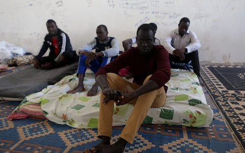 Migrants sit in a detention centre run by the interior ministry of Libya's eastern-based government, in Benghazi