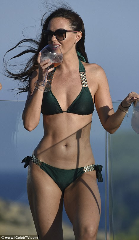 Sun, sea and sangria! The brunette bombshell seemed in good spirits as she polished off her cocktail