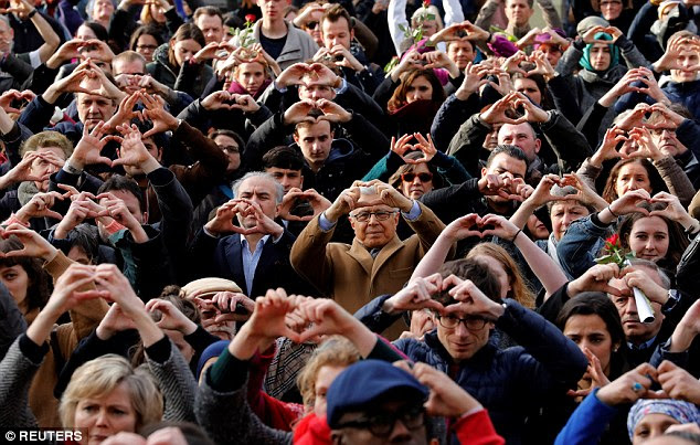 People make hearts with their hands during a ceremony in Belgium to commemorate the first anniversary of the bomb attacks in Brussels