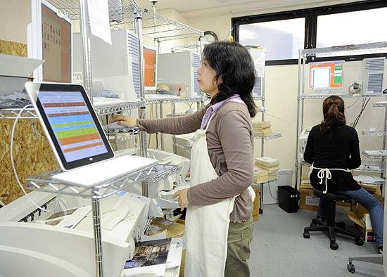 Funcionária escaneia livros na Bookscan, matriz japonesa da 1DollarScan, em Tóquio
