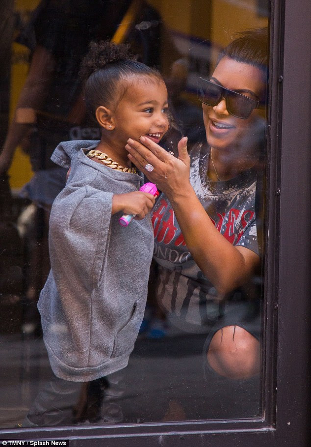 Cutie: North flashed a big smile as mom Kim laughed at her antics