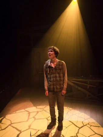 A teenager in scruffy clothing performs on stage.