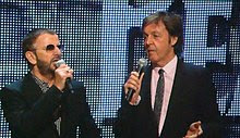 McCartney and Starr standing on a stage facing each other both with microphones help up to their mouths. Both men are wearing dark suits, McCartney is wearing a pink shirt, and Starr a black-and-white print.