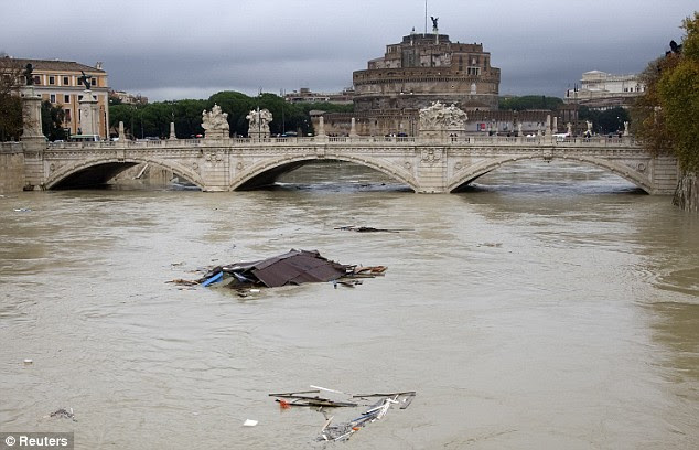 Debris floats on the Tiber river as Sant'Angelo castle is seen in background in downtown Rome today