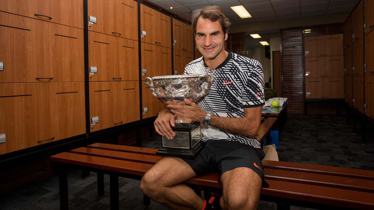 This handout photo taken and released by Tennis Australia on January 30, 2017 shows Switzerland's Roger Federer celebrating with the championship trophy inside the locker room after his victory against Spain's Rafael Nadal in the men's singles final on day 14 of the Australian Open tennis tournament in Melbourne on January 29, 2017. Fiona Hamilton / AFP