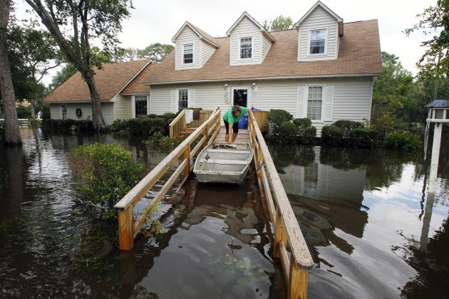 Lechelle Spalding pulls a boat up to her flooded home after a storm surge on the Outer Banks in Kitty Hawk, N.C., Sunday, Aug. 28, 2011 in the aftermath of Hurricane Irene after it left the North Caro
