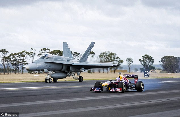 Blink and you'll miss it: A Red Bull F-1 car goes up against an Australian Air Force F-18 fighter jet