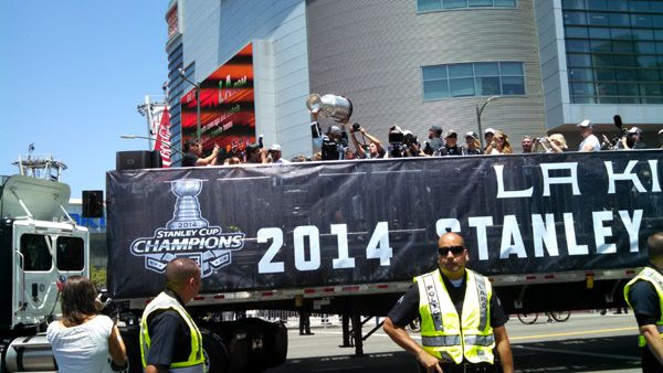 Los Angeles Kings center Anze Kopitar hoists up the Stanley Cup trophy as the flatbed truck carrying the 2014 NHL champions approaches STAPLES Center during their victory parade...on June 16, 2014.