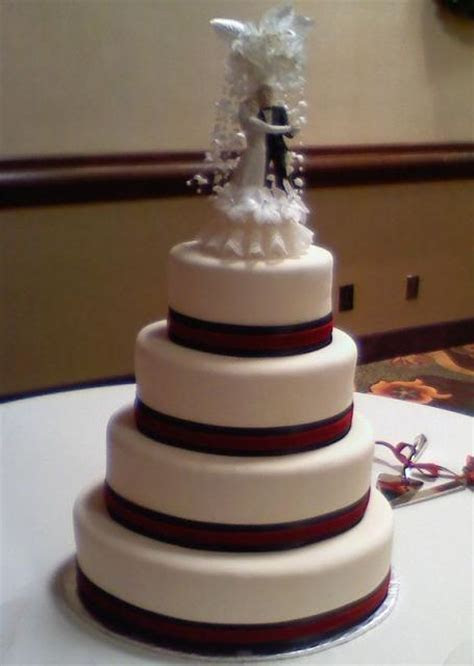 Four tier white wedding cake with bride and groom topper