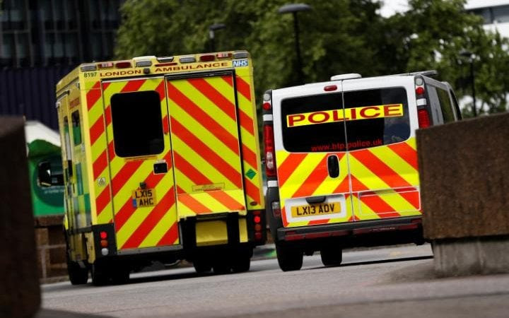Ambulance waits next to a police car outside the ER at St Thomas' Hospital in London