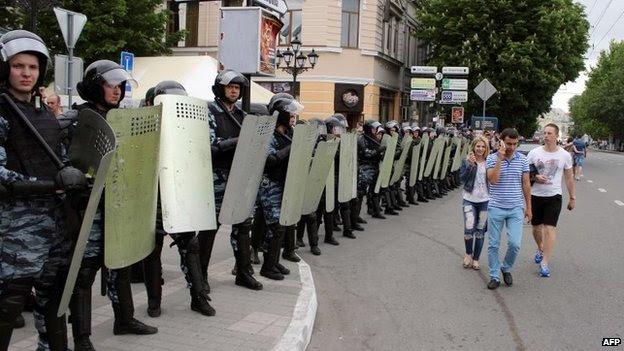As pessoas passam por oficiais da força de polícia de choque russa OMON bloqueando uma rua na capital da Criméia Simferopol