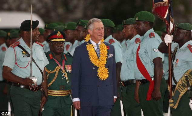 Prince Charles inspects the honour guard after arriving in Port Moresby on a three-day tour of Papua New Guinea