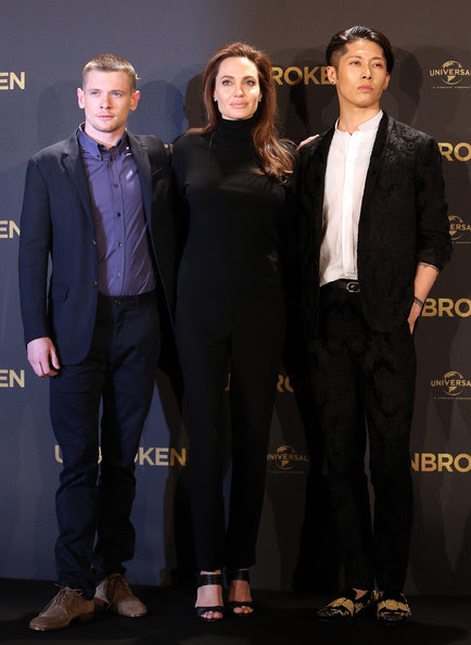 Angelina Jolie (L to R) Jack O'Connell, Angelina Jolie and Miyavi pose at a photocall for the film 'Unbroken' on November 27, 2014 in Berlin, Germany.