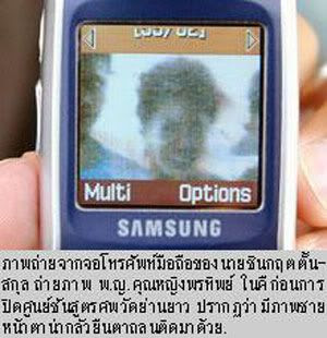 This is a Photoshopped pic assuming someone e-mailed this image to this dude's cell phone.  If not, then how convenient that the ghost is smiling for the camera too!  Verizon LG should follow Samsung's lead... They'd both be making billions if they could build camera phones that can photograph dead people!  Anyways, this photo actually appeared in a Thai newspaper.