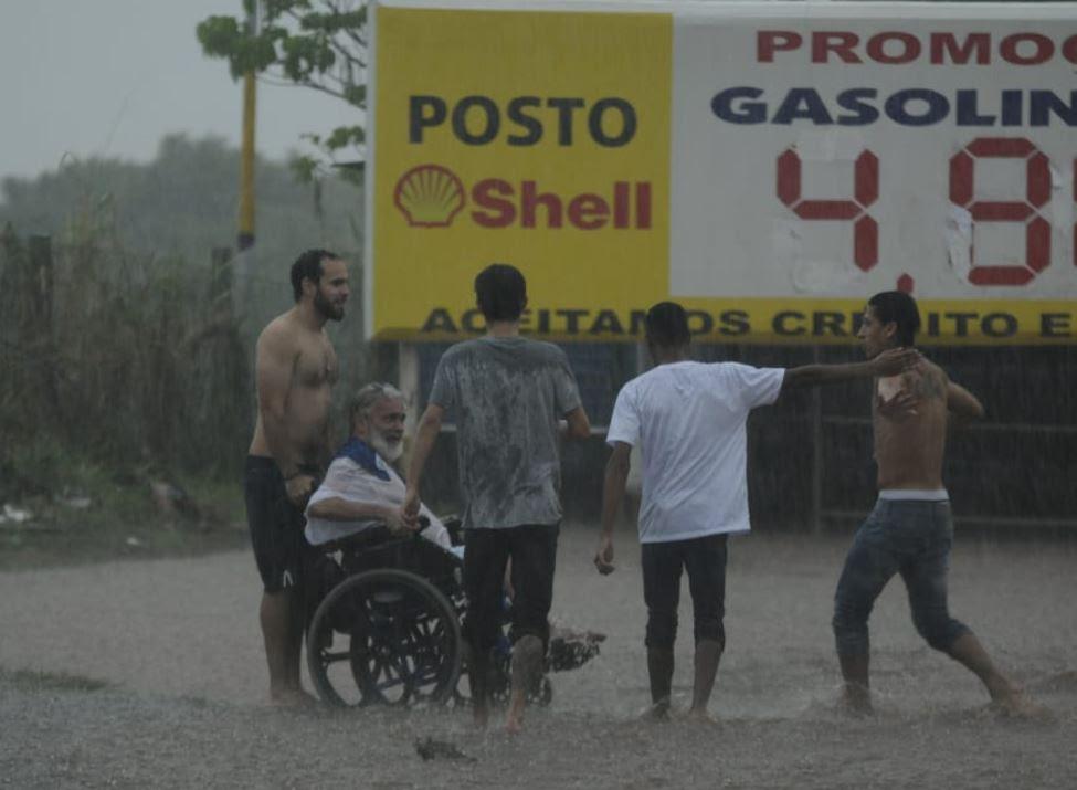 meio chuva, jovens ajudam cadeirante atravessar rua