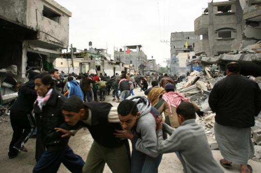 Palestinians ran yesterday during an Israeli airstrike at the Jabalia refugee camp in northern Gaza Strip.