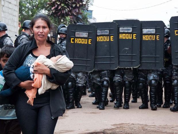 Mulher deixa o terreno com filho ao colo durante ação policial no Jardim Iguatemi (Foto: Peter Leone/Futura Press/Estadão Conteúdo)