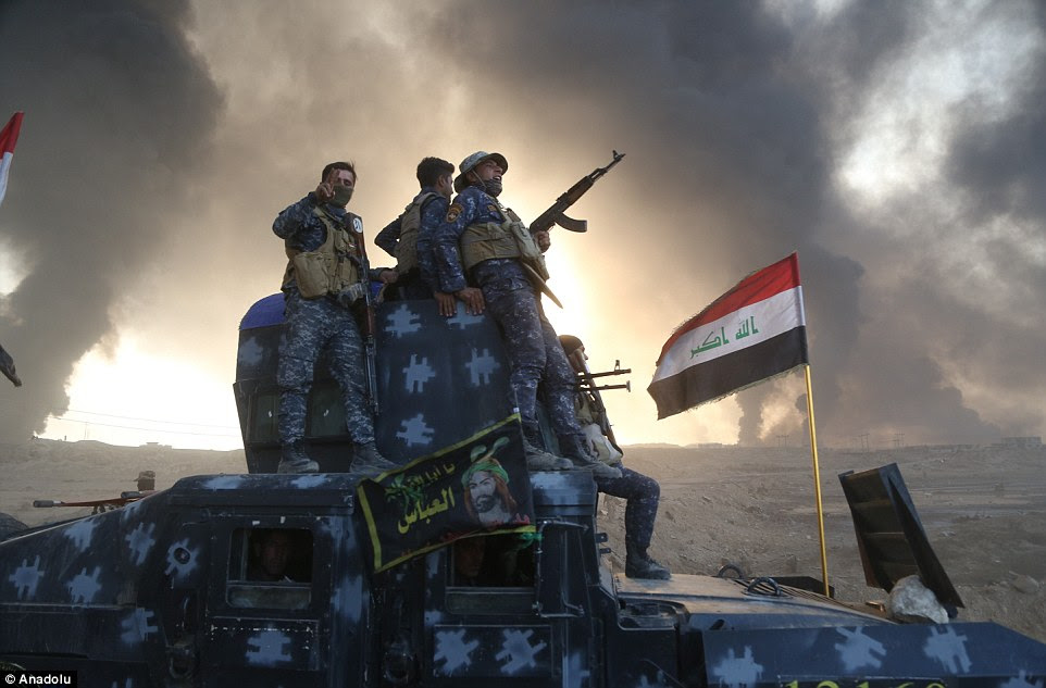 A vehicle full of Iraqi soldiers arrive in Hut as an Iraqi flag is seen planted in the ground two years after the army's defeat there