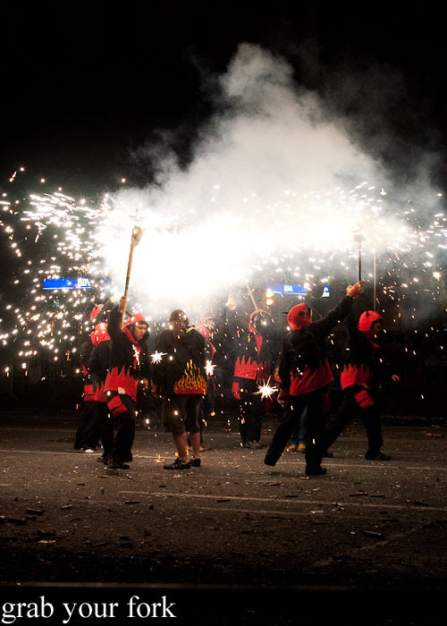 Diables devils in red and black spraying fireworks at Correfoc Fire Run for La Merce 2013