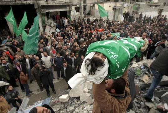A relative carried the body of one of five young sisters who authorities said died in an air strike at Gaza's Jabalya refugee camp.
