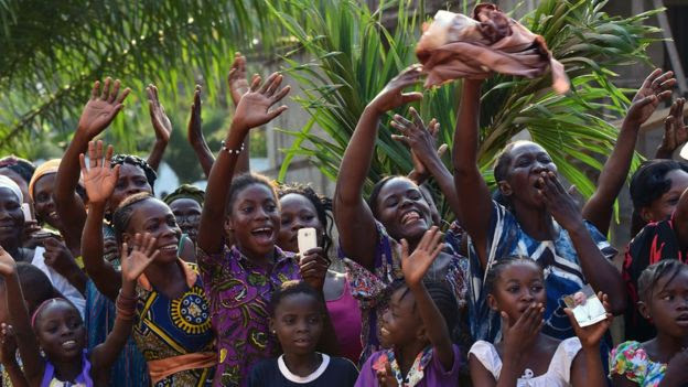 People react during the visit of Pope Francis at the Evangelic community in Bangui