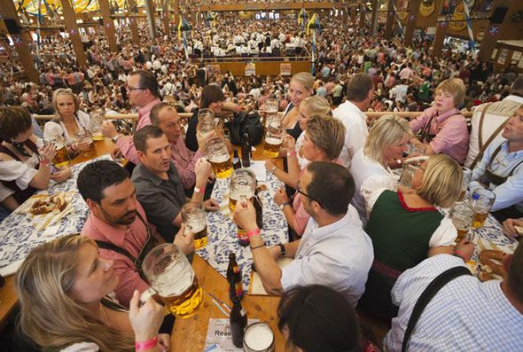 Revellers drink beer and eat German sausages at Oktoberfest