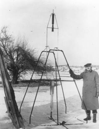 Robert Goddard posa al lado de su primer cohete de combustible  líquido antes de su lanzamiento el 16 de Marzo de 1926.