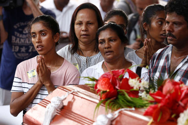 Slide 1 of 35: People attend a mass burial of victims, two days after a string of suicide bomb attacks on churches and luxury hotels across the island on Easter Sunday, at a cemetery near St. Sebastian Church in Negombo, Sri Lanka April 23, 2019.   REUTERS/Thomas Peter