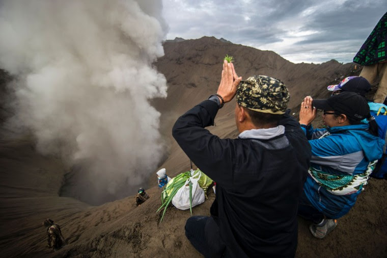 Devotees climb active volcano to offer food and livestock to Hindu deity