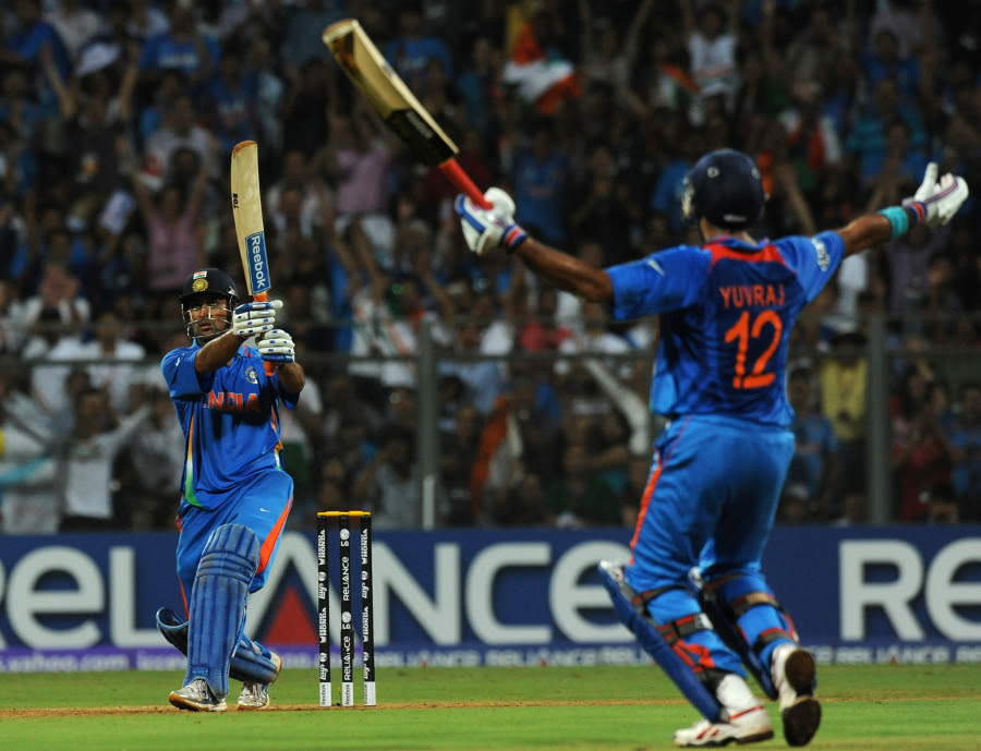 MS Dhoni watches the winning six sail over the boundary as Yuvraj Singh raises his arms in triumph