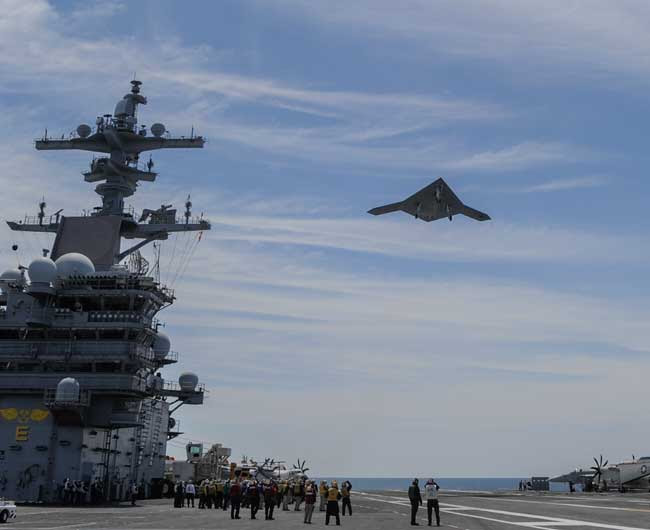An X-47B Unmanned Combat Air System (UCAS) demonstrator flies over the aircraft carrier USS George H.W. Bush (CVN 77). George H.W. Bush is the first aircraft carrier to successfully catapult launch an unmanned aircraft from its flight deck. (Photo: Northrop Grumman by Alan Radecki)