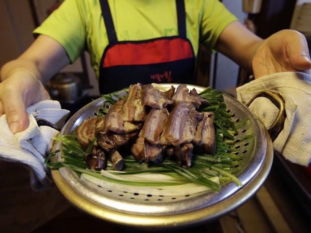 Funcionária mostra prato com carne de cachorro do restaurante Daegyo (Foto: Lee Jin-man/AP)