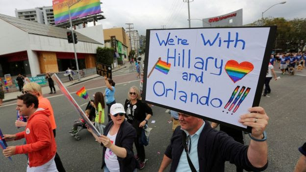 A man holding a 'we're with Hillary and Orlando' sign