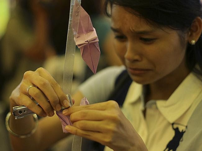 Family...A woman breaks into tears as she places a paper crane as a symbol for hope and h