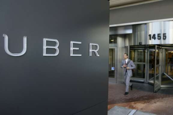 FILE - In this photo taken Tuesday, Dec. 16, 2014, a man leaves the headquarters of Uber in San Francisco. A federal judge granted class-action status Tuesday, Sept. 1, 2015, to a lawsuit in California against Uber over the payment of its drivers, upping the stakes for the ride-hailing company in the case. (AP Photo/Eric Risberg, File)