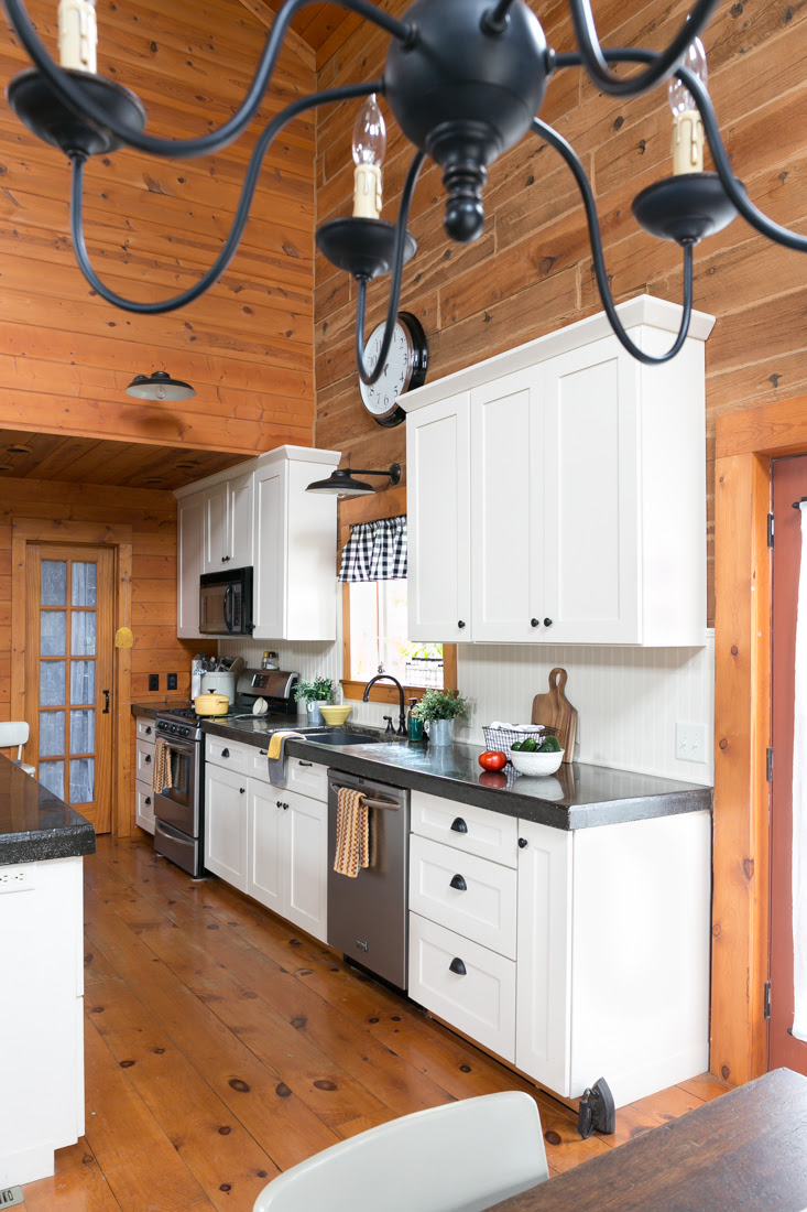 Log Home Kitchen With White Cabinets, Beadboard, and Black ...