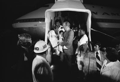 """President Ford carries a Vietnamese baby from """"Clipper 1742,"""" one of the Operation Babylift planes that transported approximately 325 South Vietnamese orphans from Saigon to the United States."""