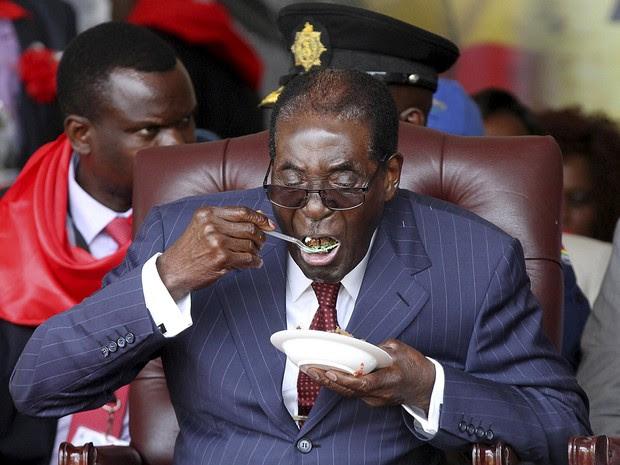 Robert Mugabe come bolo em sua festa de aniversário de 92 anos no Zimbábue (Foto: Philimon Bulawayo/AFP)