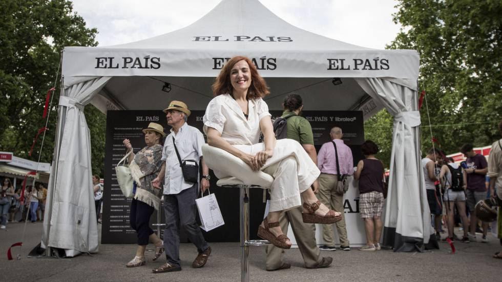Elvira Lindo, sentada frente al estand de EL PAÍS en la Feria del Libro.