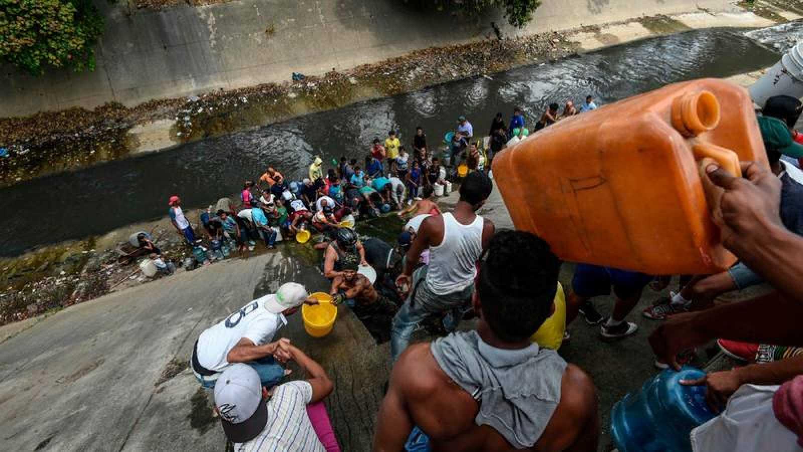 Un grupo de personas recoge agua de un canal en Caracas tras el apagón en Venezuela