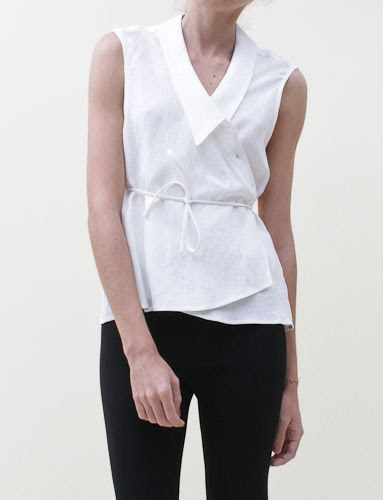 Creatures Of Comfort flow top with a collared deep plunge in front. Four buttons for closure covered by flap and sewn on optional wrap ties. Loop hole for wrap to go through sewn along right side of seam.